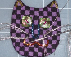 sewing whiskers to cat face