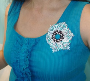yo yo flower pinned to blouse
