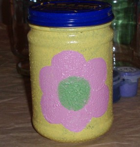 pink flower with green center on glass jar