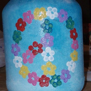 painting flowers on peace sign jar