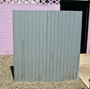 trash cans hidden behind fence made from roofing panels