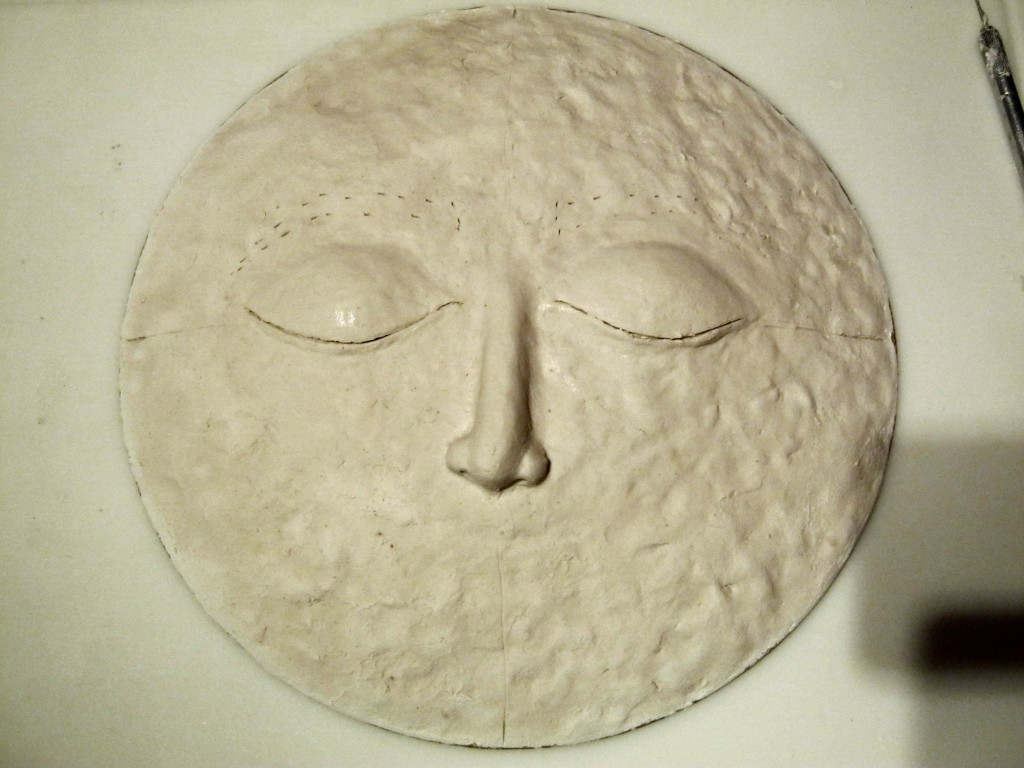 Both eyes done on moon sculpture, marks for eyebrows