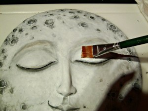 Adding another layer of white paint to moon sculpture