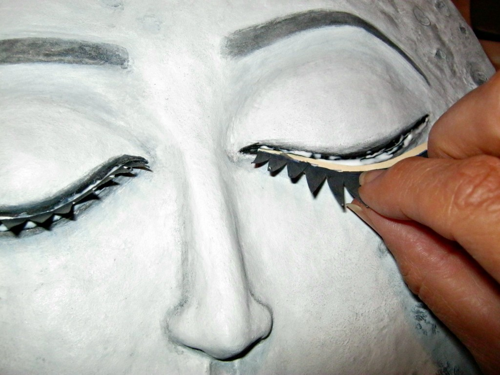 Gluing eyelashes to moon sculpture
