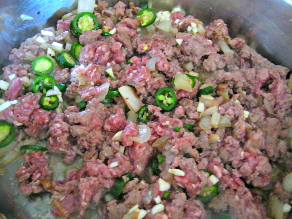 Browning the meat, onions and garlic with a few jalapenos