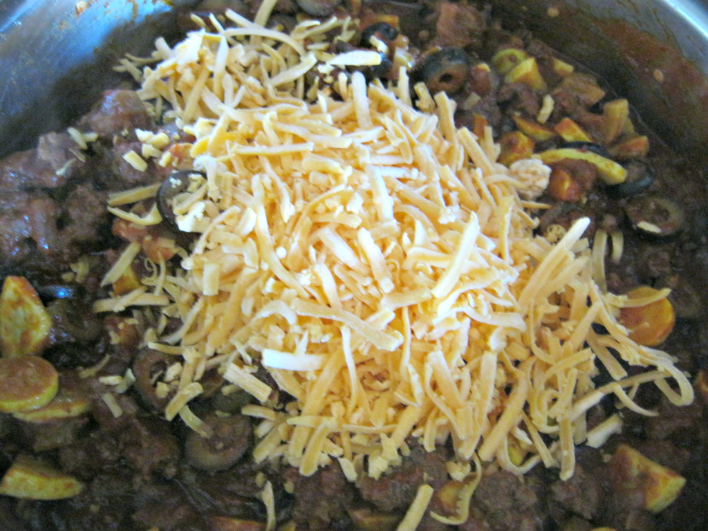 Adding grated cheese to tamale squash pie