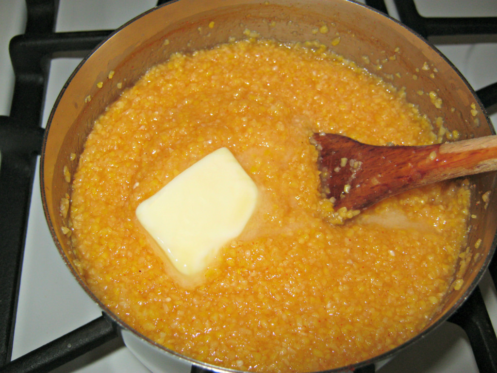 Adding butter to cooked corn meal