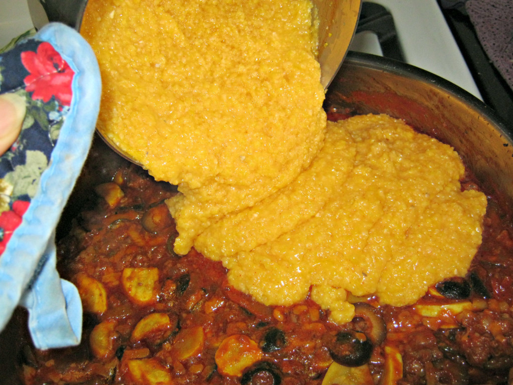 Cooked corn meal goes on top of meat mixture
