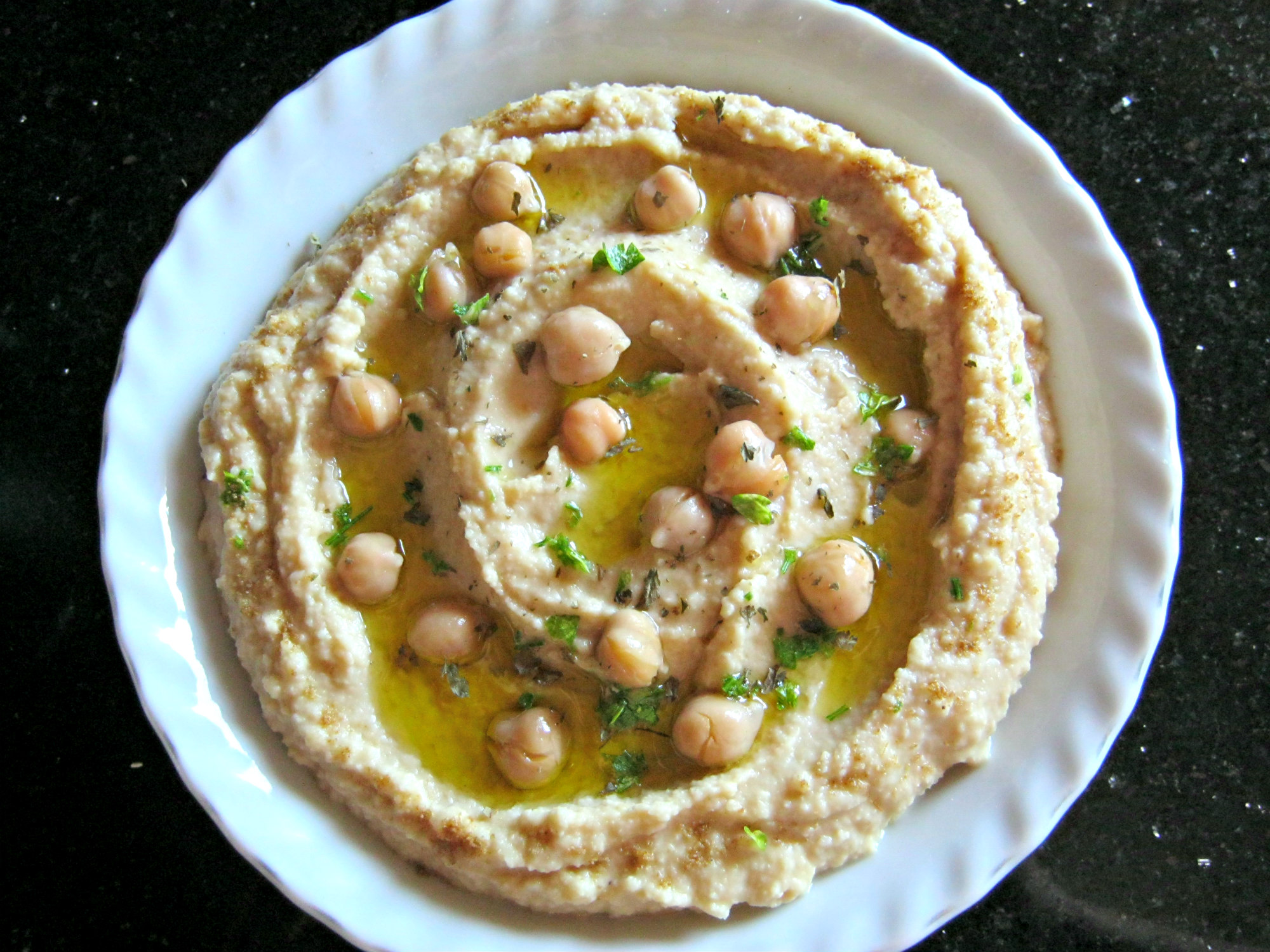 Hummus garnished with olive oil, parsley flakes and ground cumin