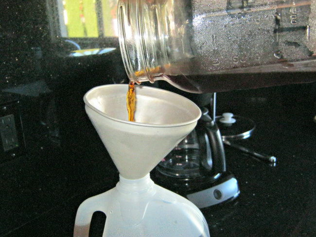 Pouring brewed coffee into plastic jug